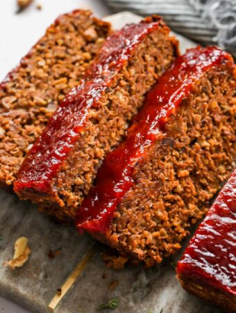 Three slices of vegan meatloaf on a cutting board