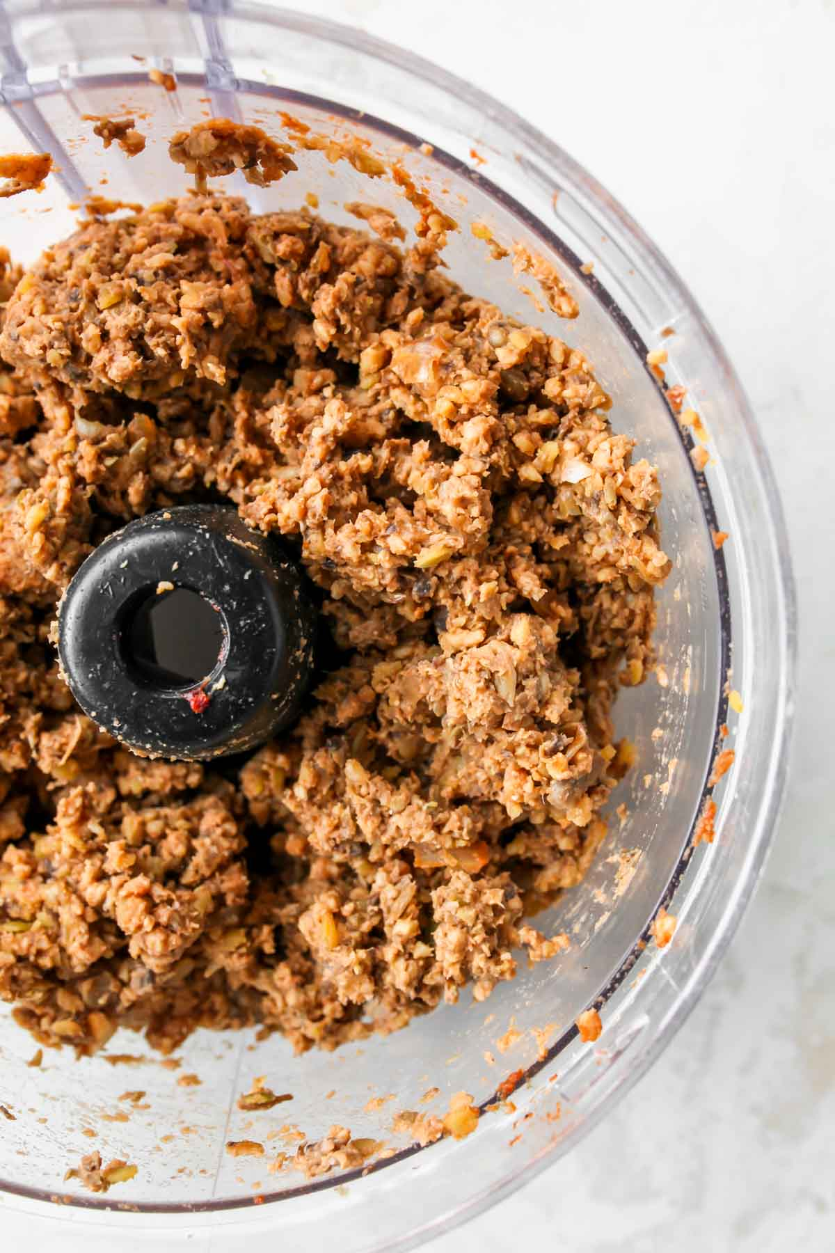 Mushroom lentil mixture in the bowl of a food processor
