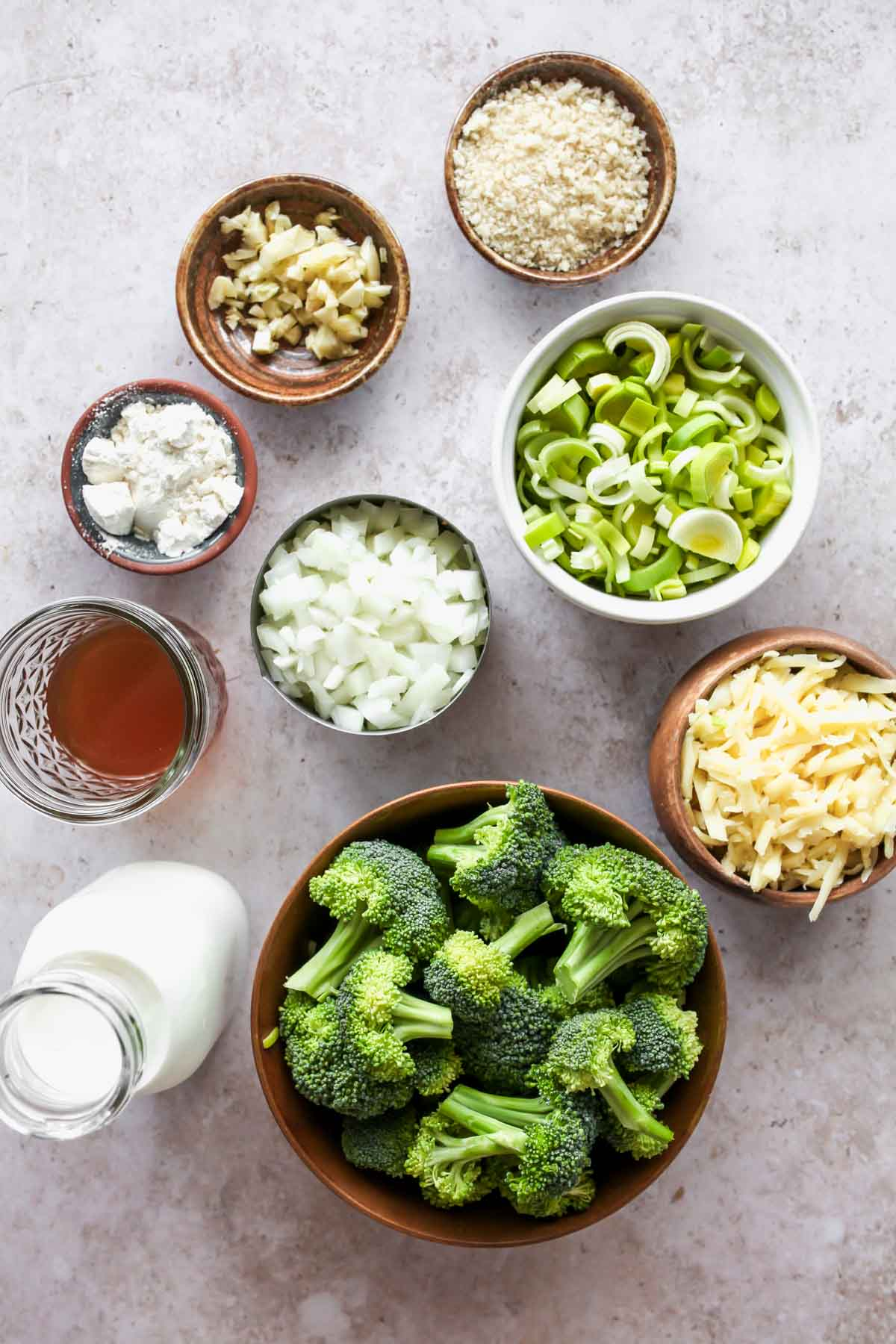 Ingredients for broccoli casserole in separate bowls on a white board