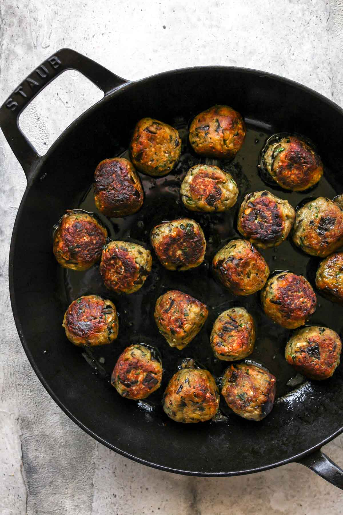 Vegetarian meatballs being seared in a large black skillet
