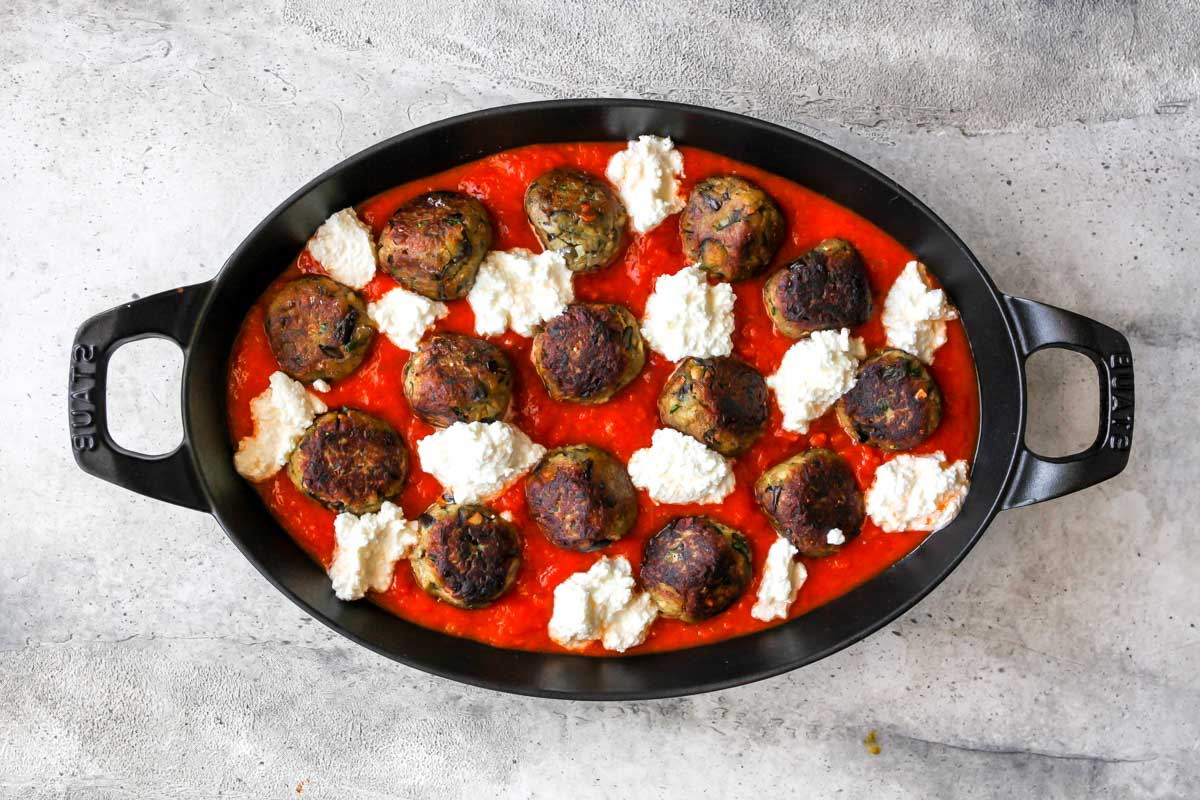 Skillet of marinara sauce, ricotta cheese, and aubergine meatballs before being baked