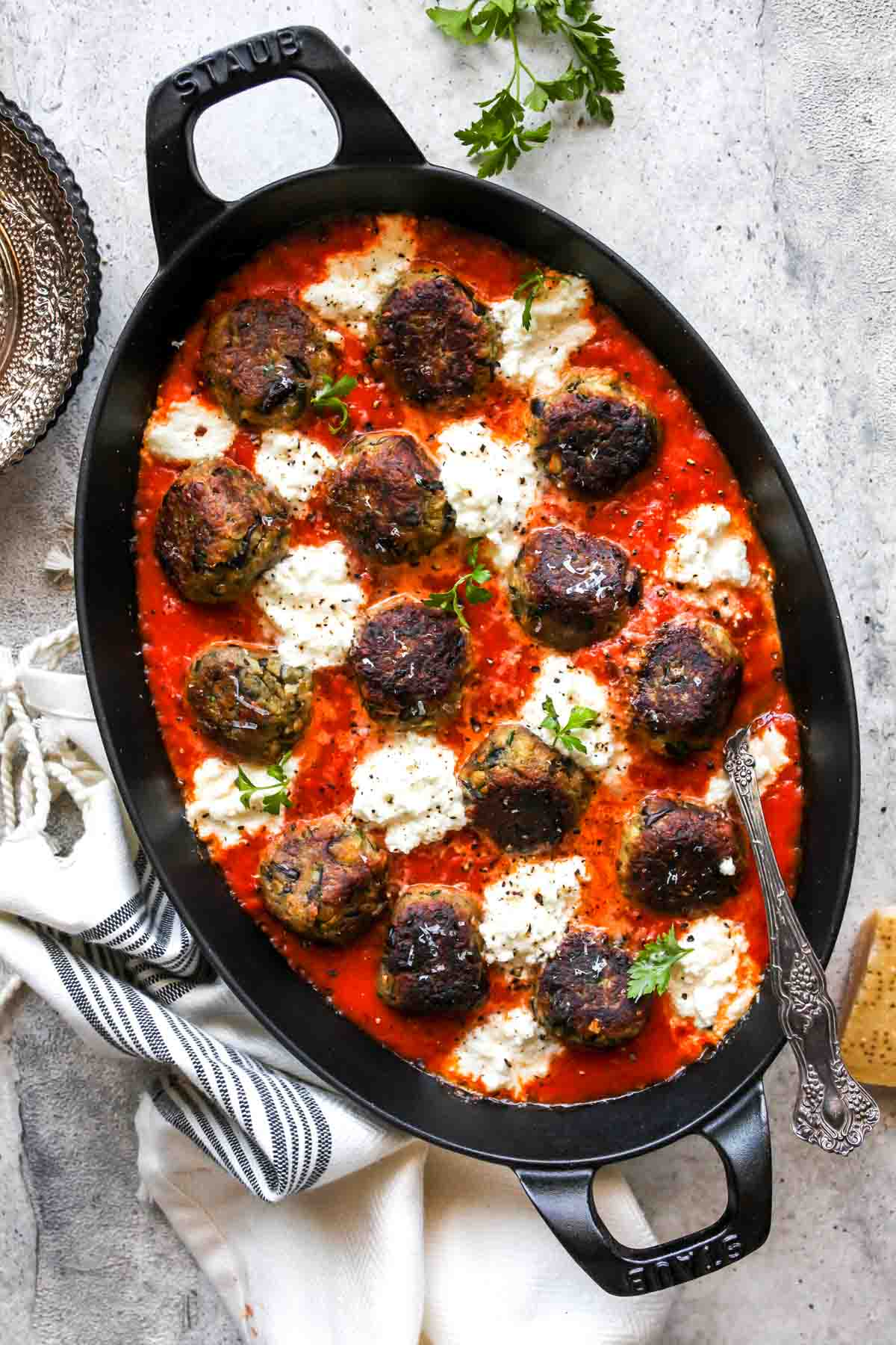 Vegetarian meatballs in a black baking pan with marinara sauce and ricotta