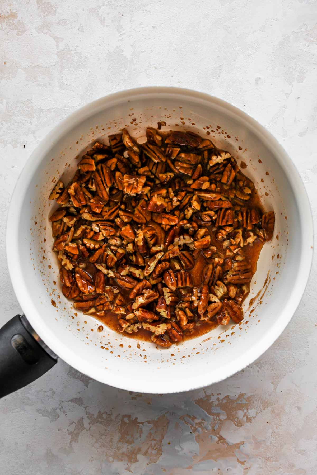 Pecans, maple syrup, and spice simmering in a saucepan