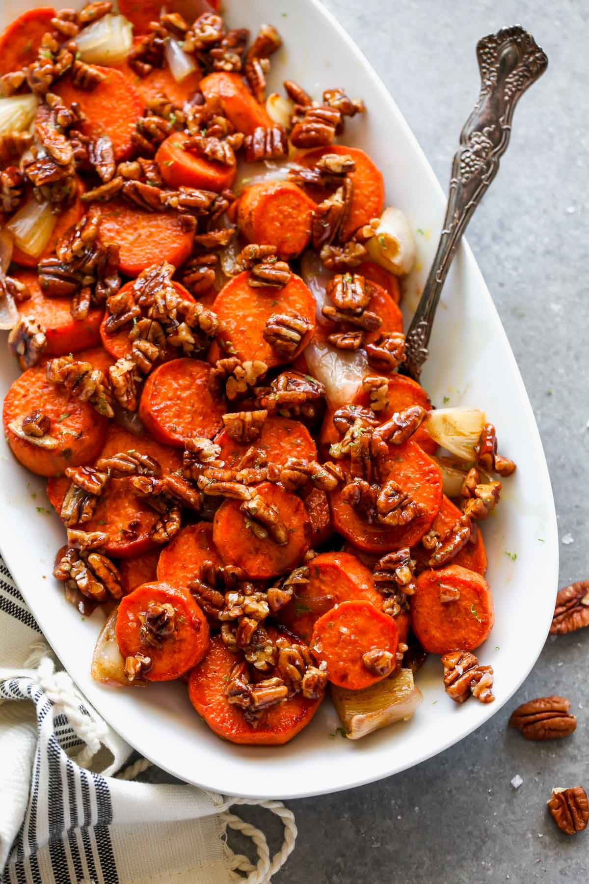 Sweet potato coins on a white platter topped with pecan praline