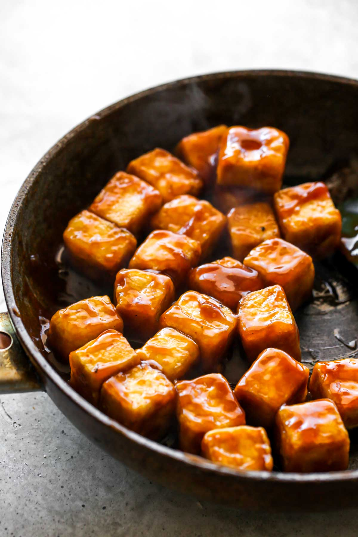 Tofu cubes being coated in orange sauce in a skillet