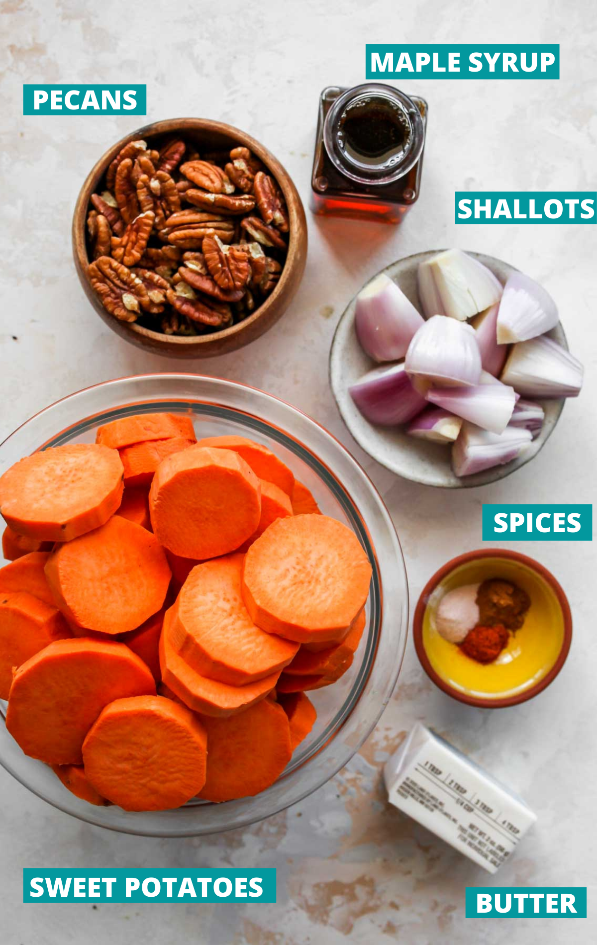 Sweet potatoes, pecans, shallots, and spices in separate bowls with blue labels