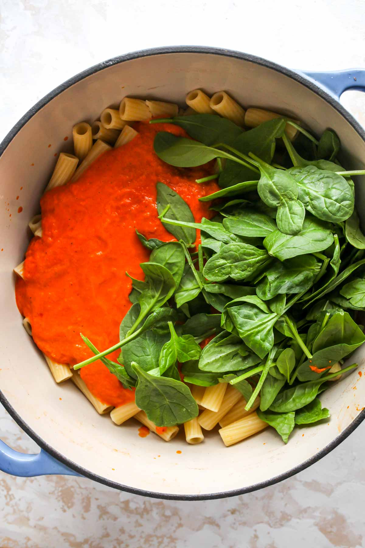 Rigatoni, spinach, and red pepper sauce being mixed in a large pot