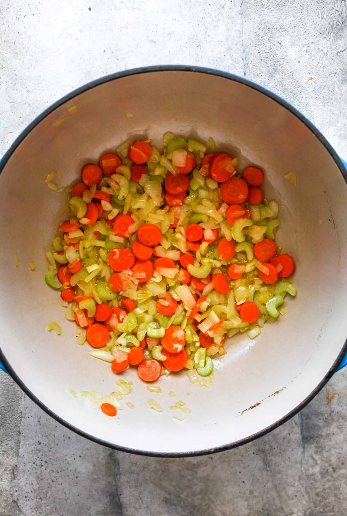 Onion, carrots, and celery sauting in olive oil in a Dutch oven