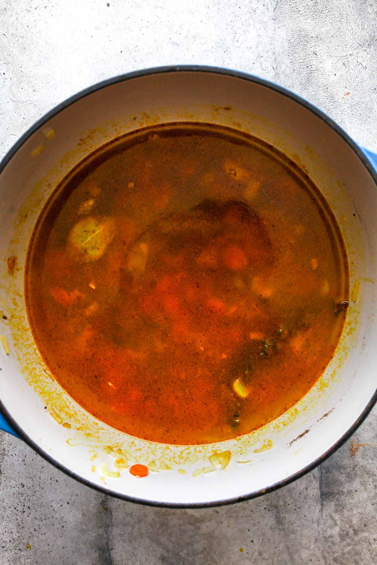 Broth being added to a Dutch oven