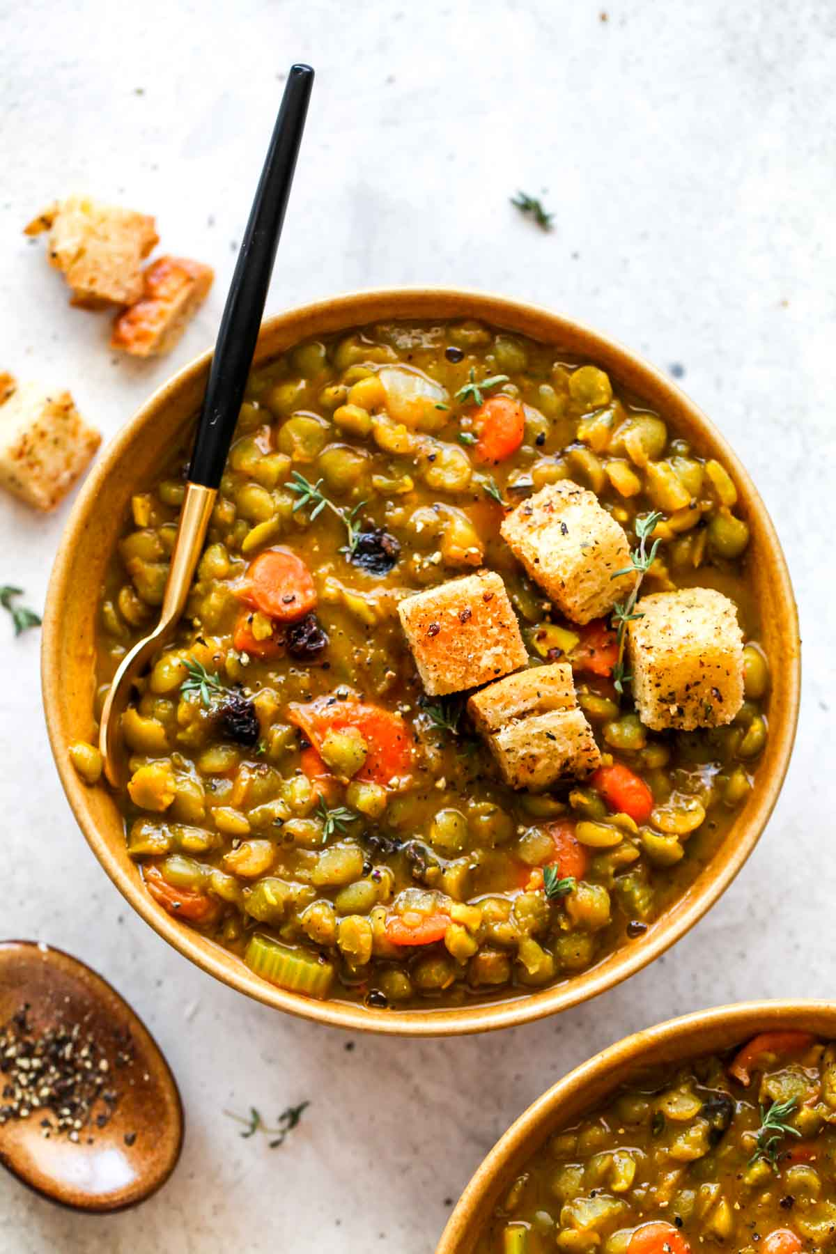 Gold bowl filled with split pea soup topped with croutons