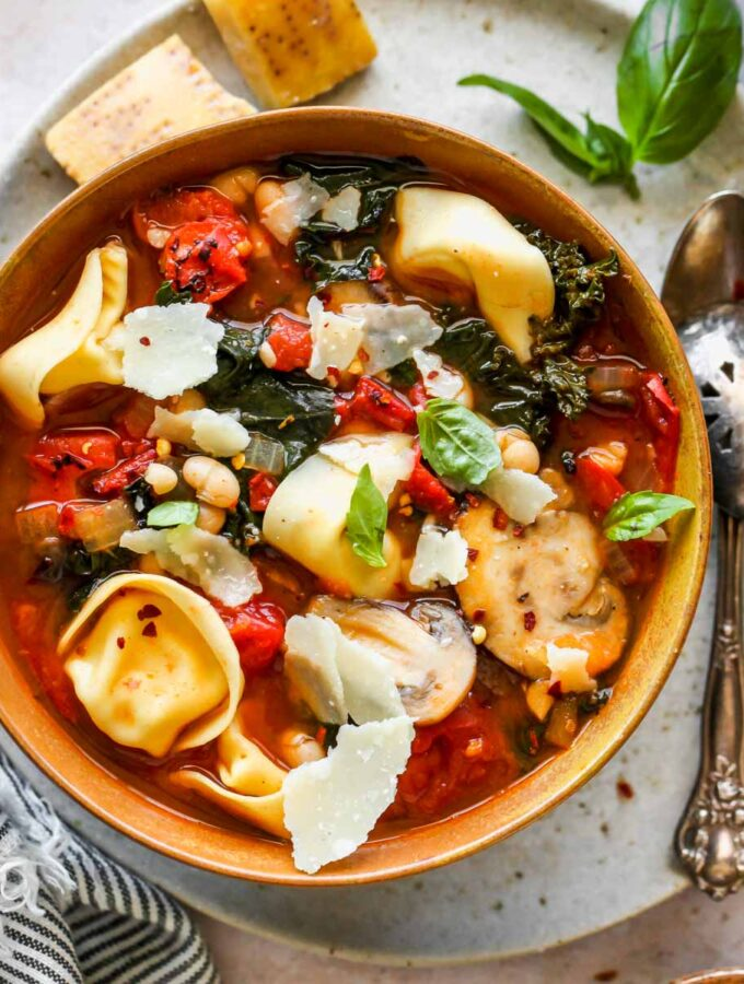 Tuscan tortellini and tomato soup in a gold bowl with basil garnish