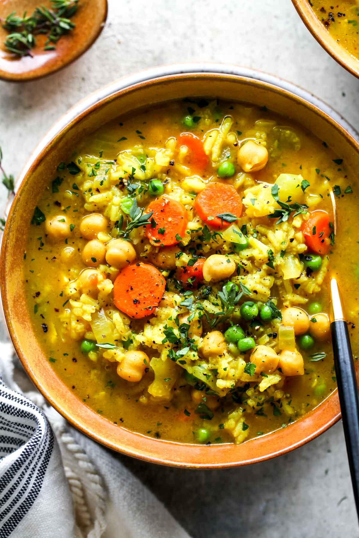 Chickpea and rice soup in a gold bowl topped with fresh thyme