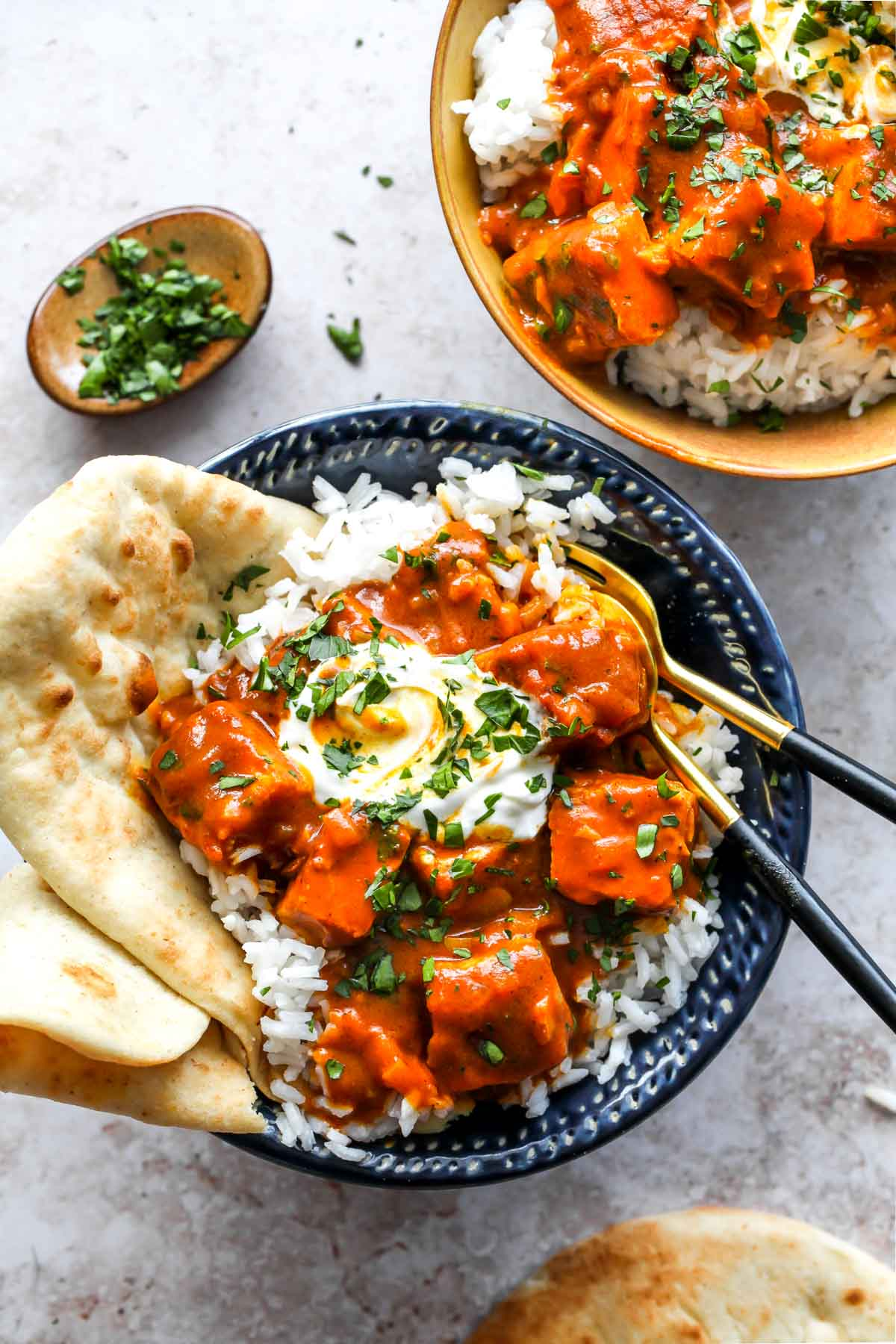 Two bowls of vegan tikka masala topped with yogurt, herbs, and naan bread