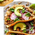 Vegan chorizo tacos topped with avocado and cilantro