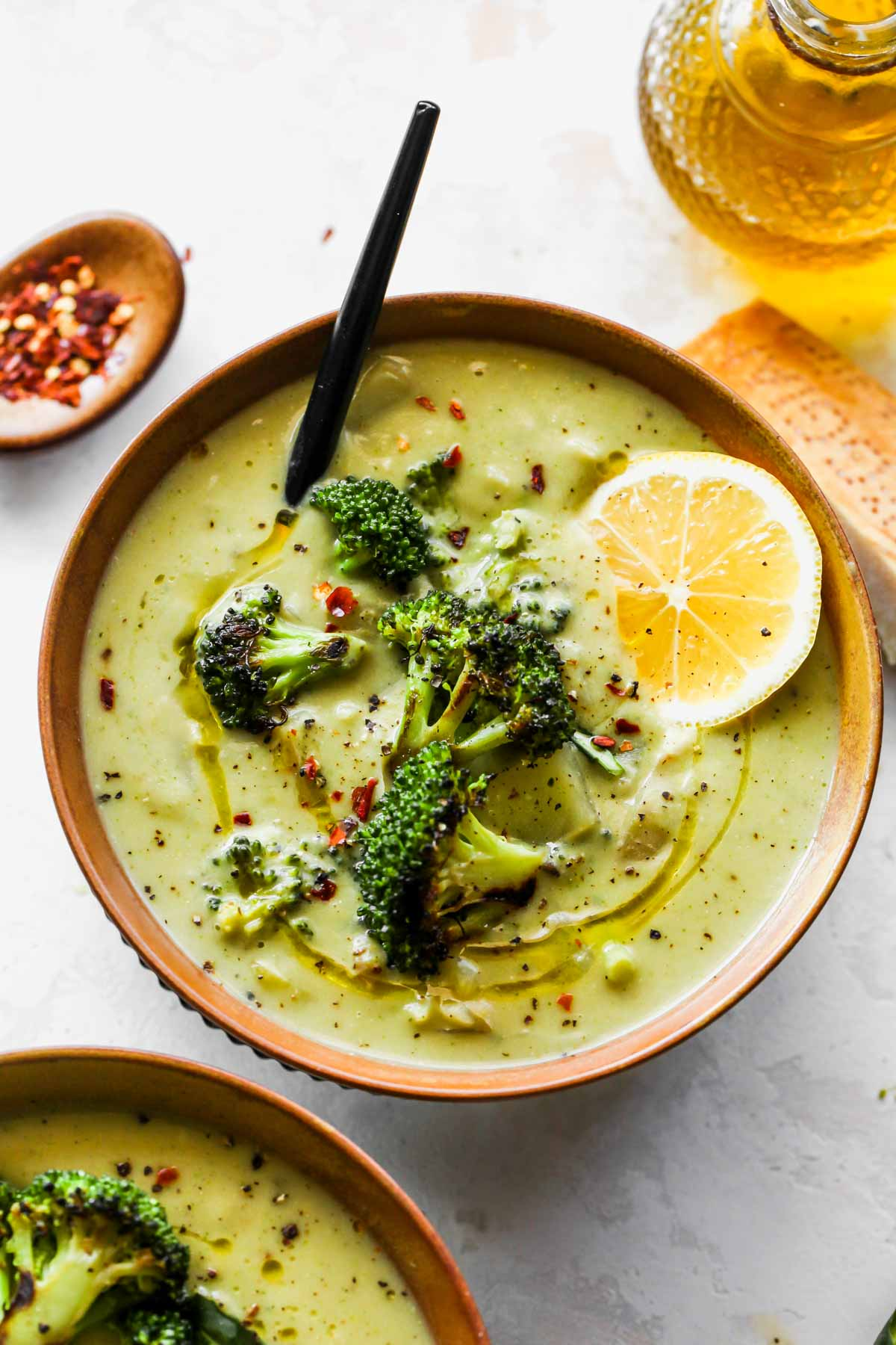 Two bowls of creamy broccoli soup topped with broccoli florets and chili flakes