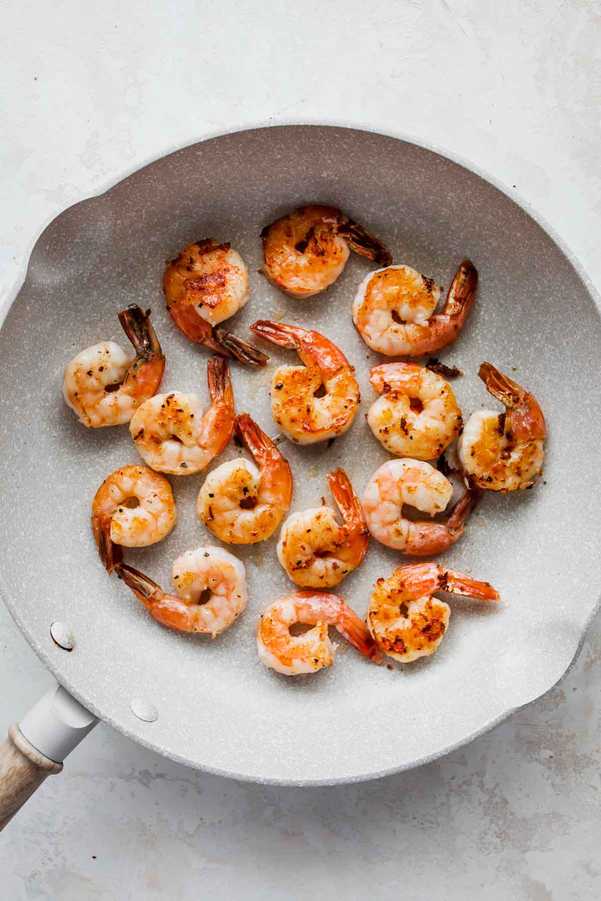Prawns being pan-seared in a large white skillet
