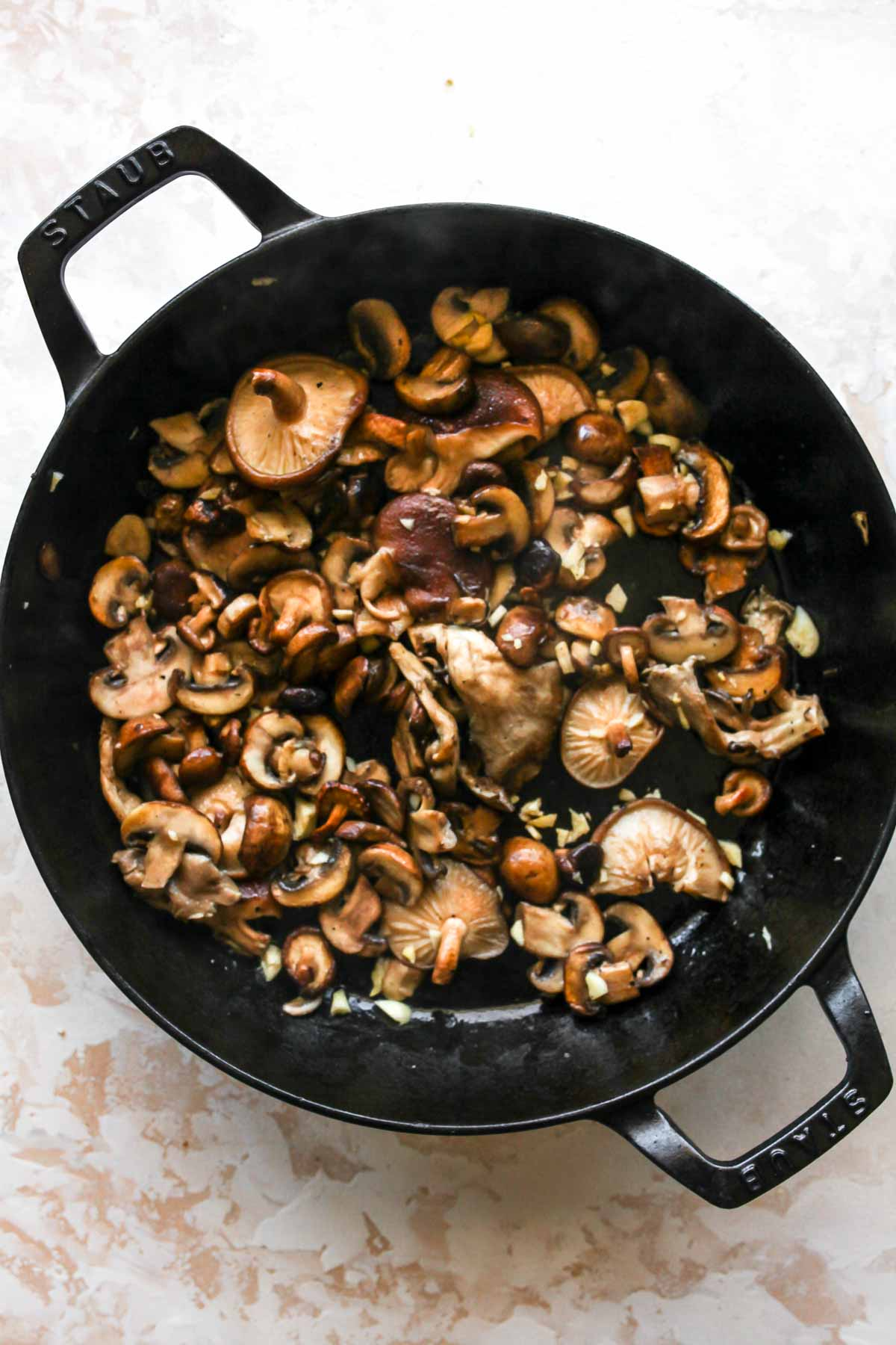 Mushrooms being sauteed in a cast-iron skillet