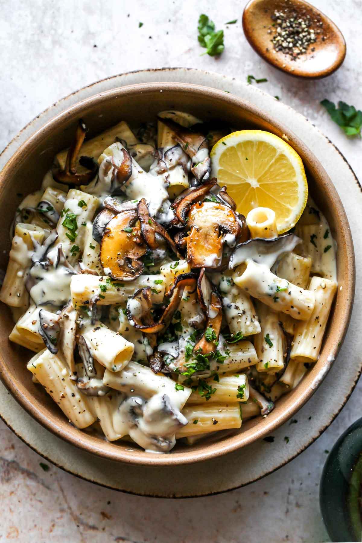 Mushroom pasta in a gold bowl with creamy vegan sauce