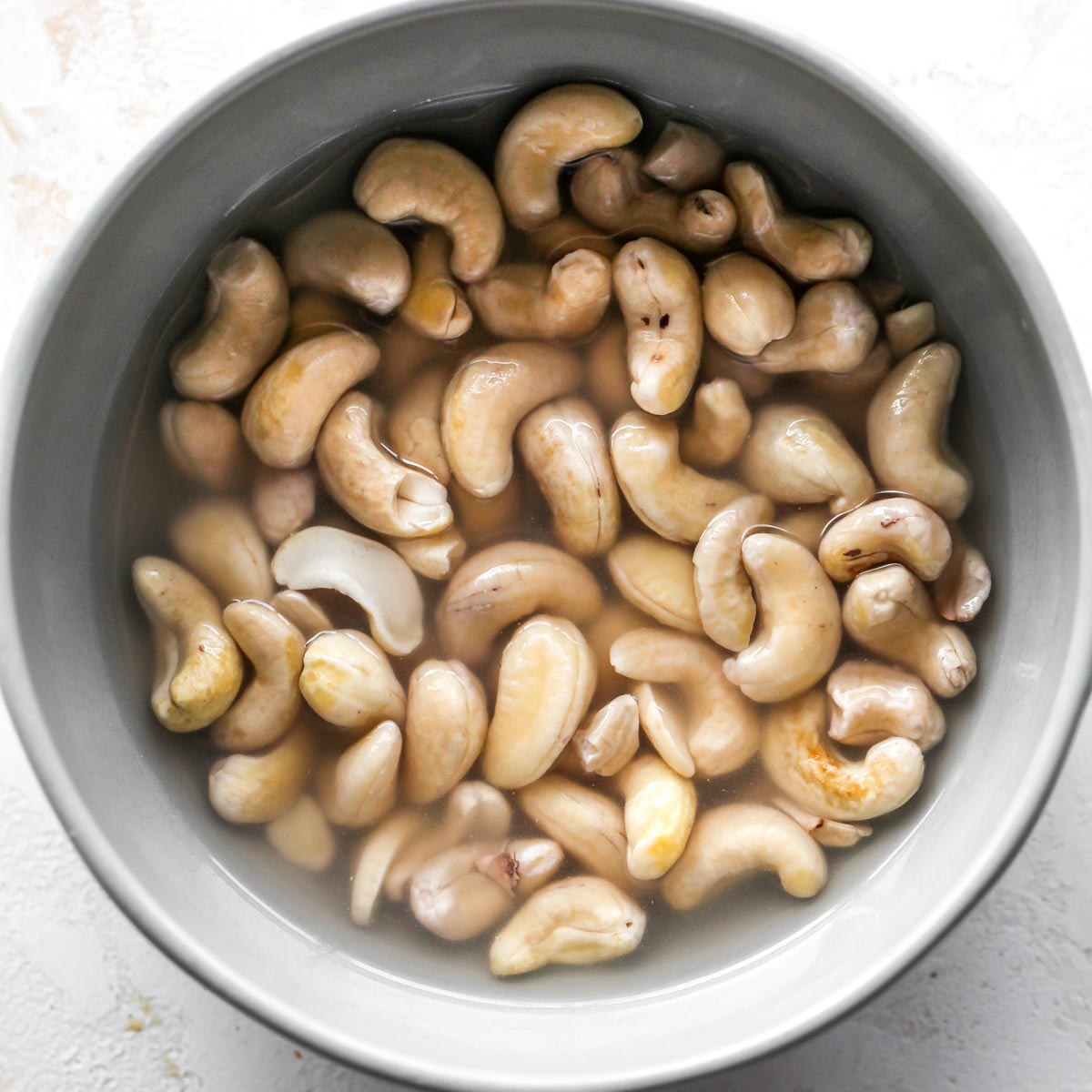 Cashews soaking in water in a grey bowl