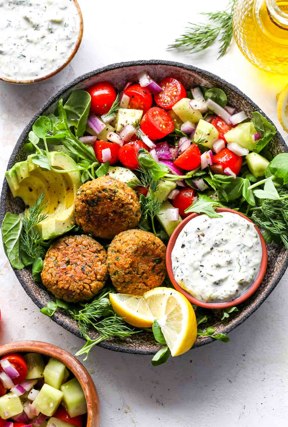 Chickpea falafel styled in a bowl with arugula, cashew tzatziki, and tomato-cucumber salad