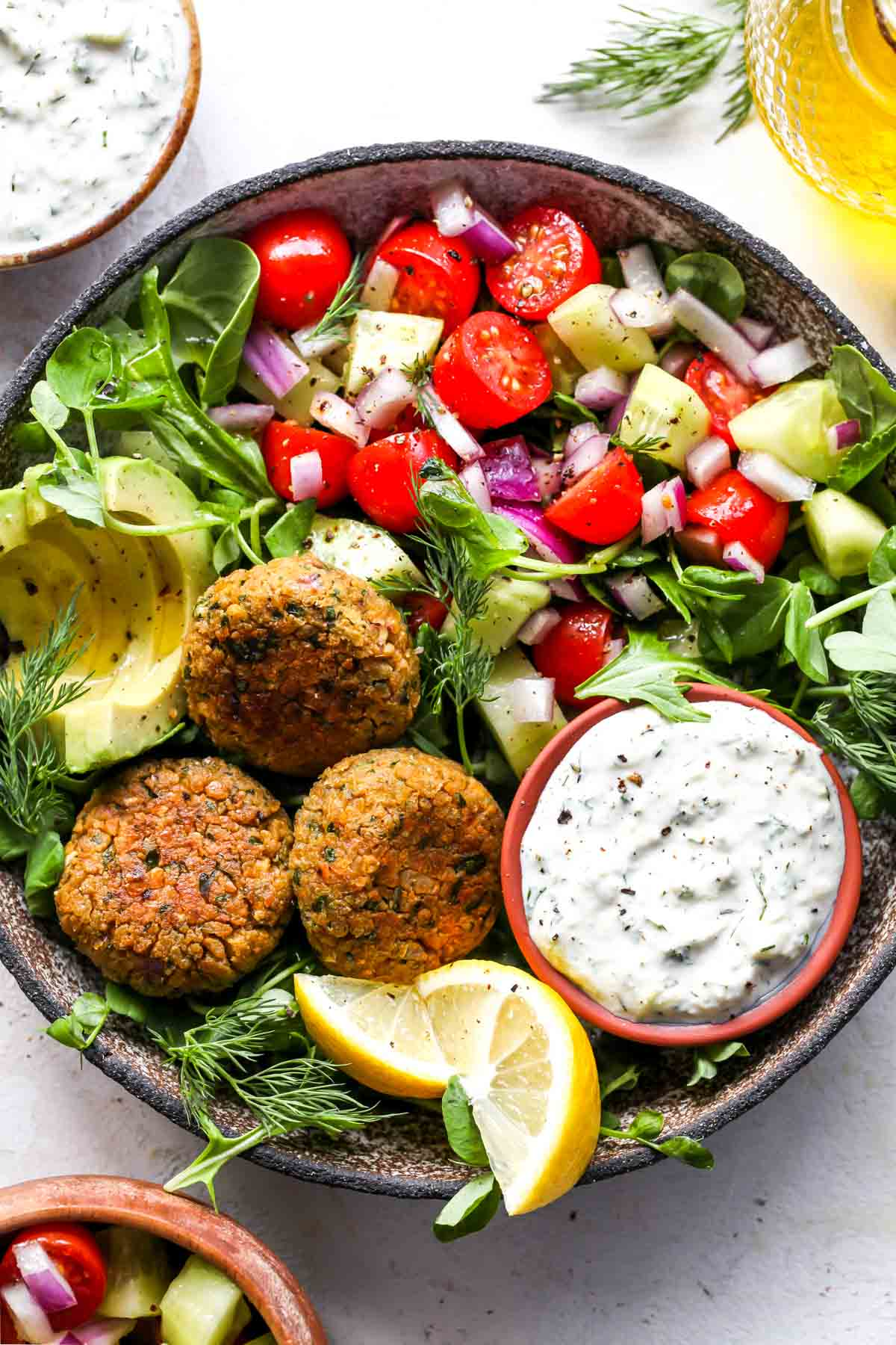 Falafel and vegan tzatziki served in a bowl with tomato salad