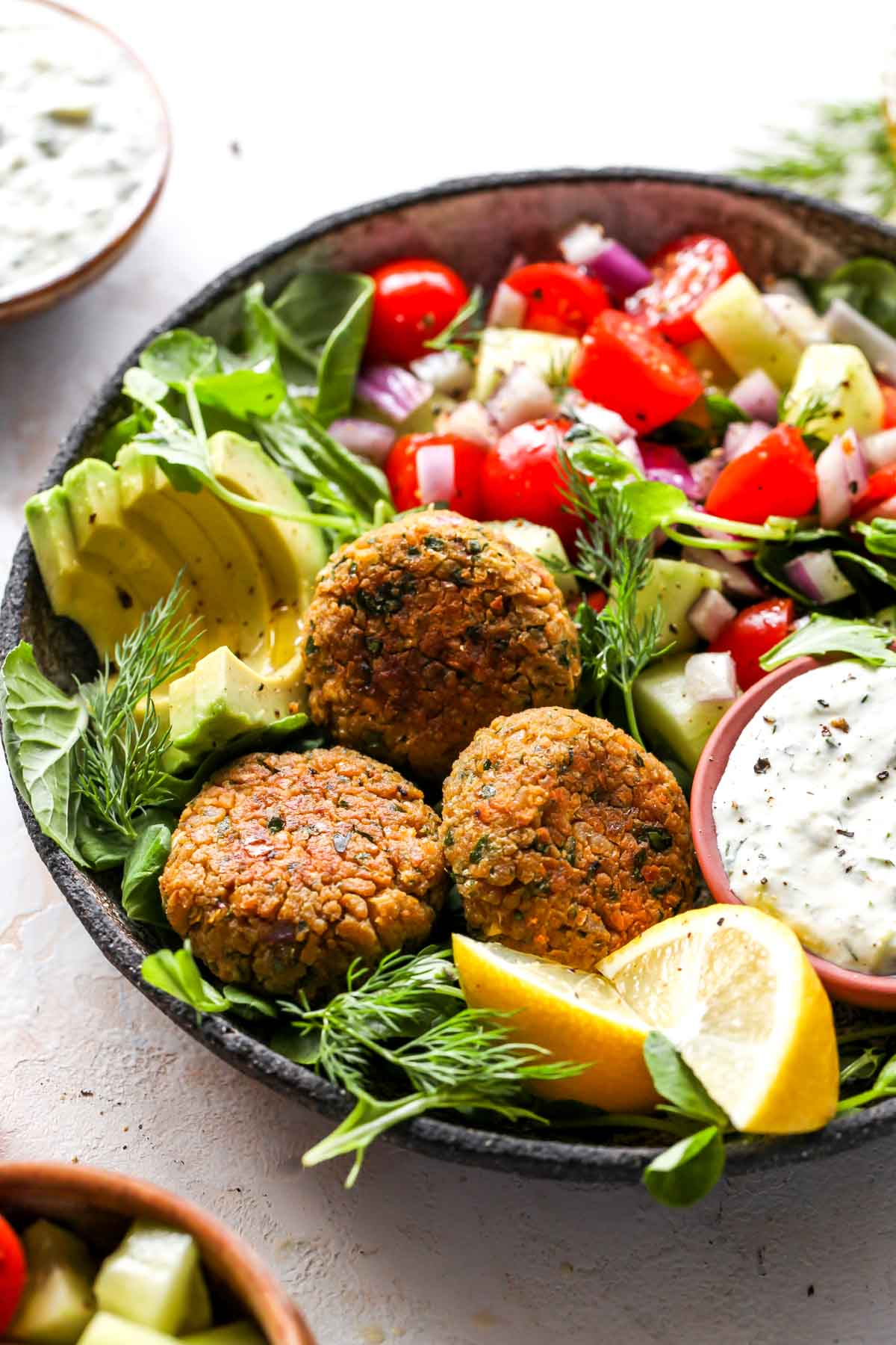 Falafel over a bed of greens with sliced avocado
