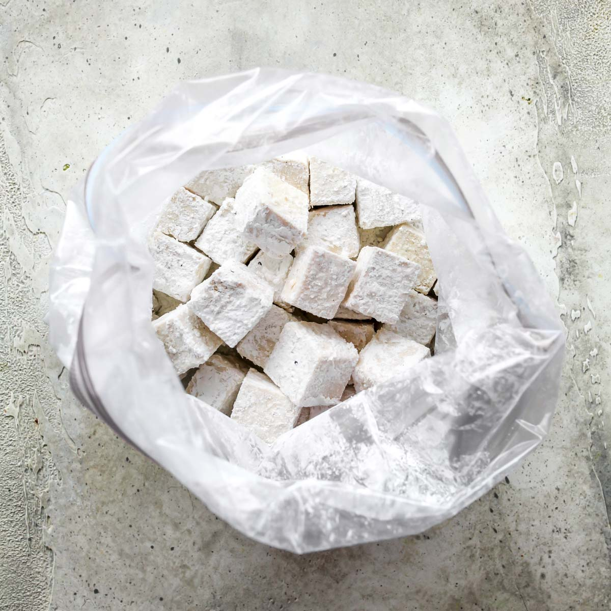 Cubes of tofu tossed in corn starch in a gallon-sized bag