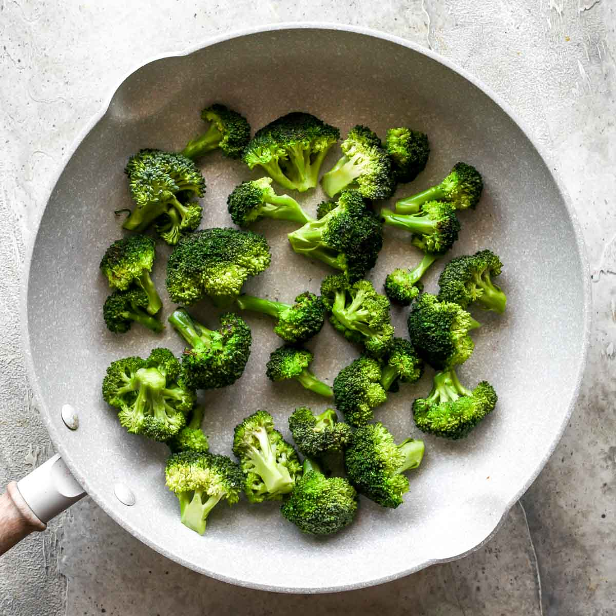 Broccoli florets being sautéed in a skillet