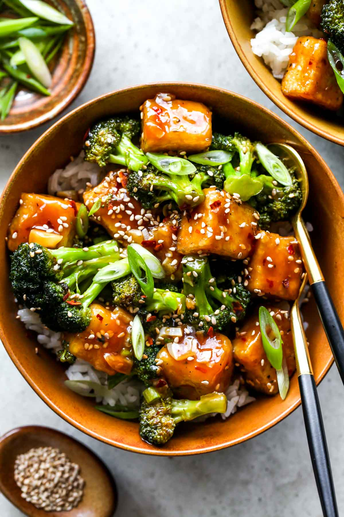 Asian tofu and broccoli in a gold bowl topped with sesame seeds