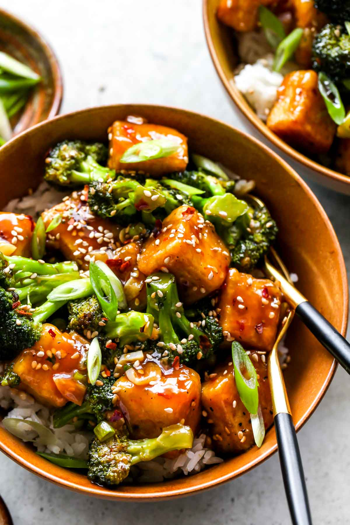 General Tso's Tofu and Broccoli served over rice in a gold bowl