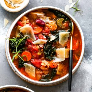 Bowl of vegetable soup with Parmesan and herb garnish
