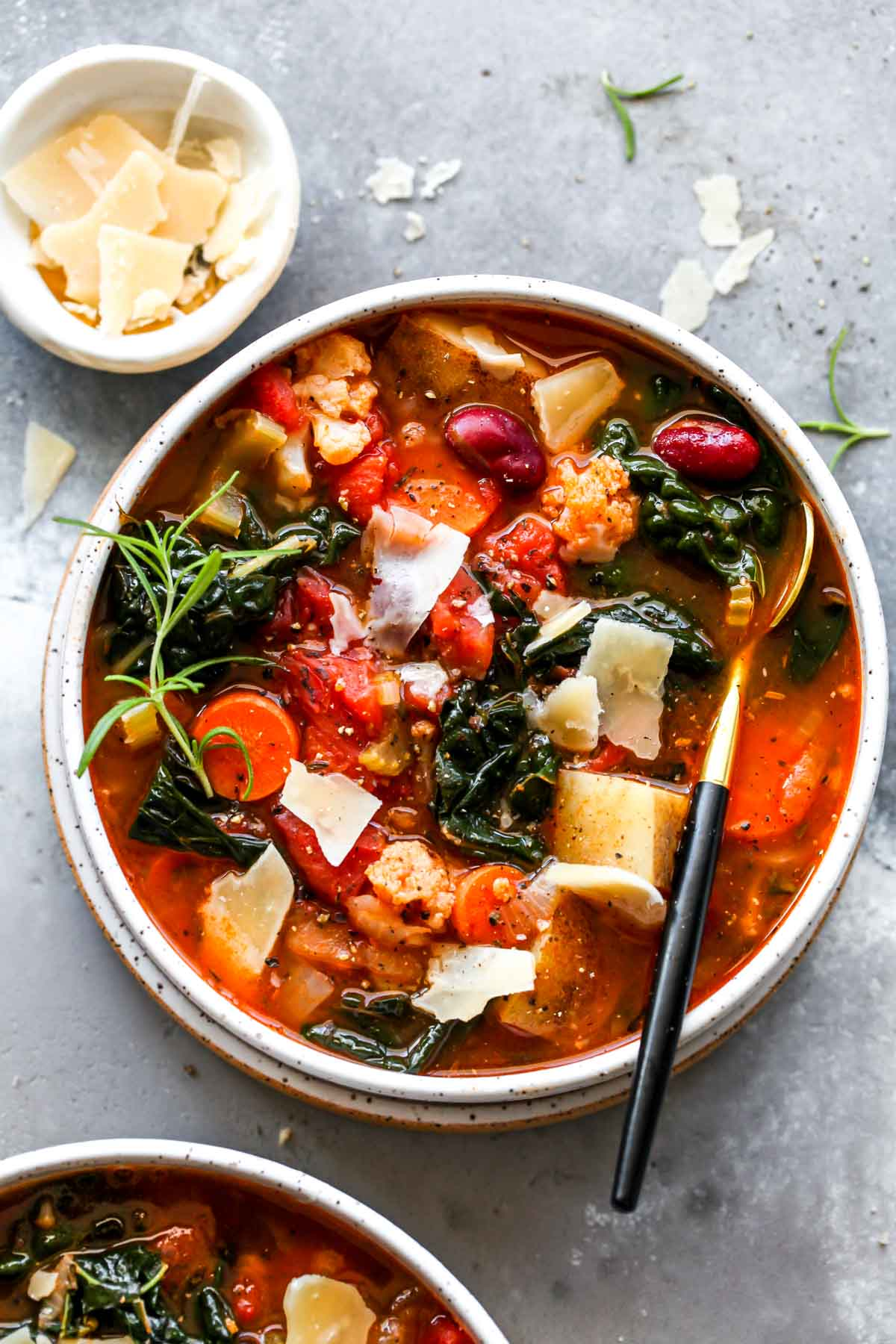 Bowl of vegetarian soup with potatoes, kale, and tomatoes