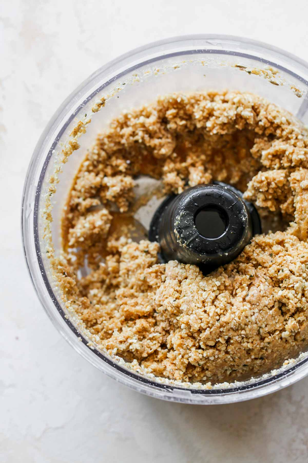 Cashew butter and maple syrup blended with dry ingredients in a food processor
