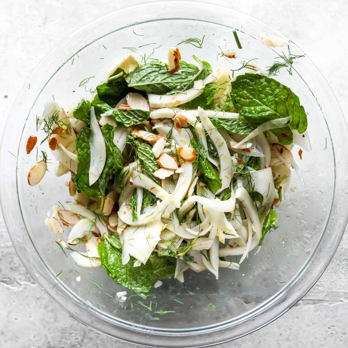 Shaved fennel, mint, and sliced almonds tossed in a clear bowl