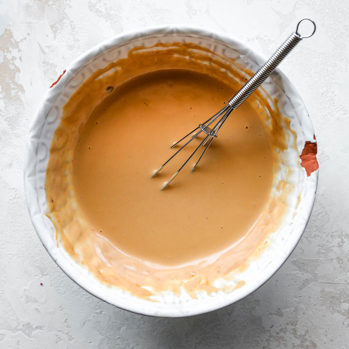 Tahini, adobo sauce, and lime juice being whisked together in a white bowl