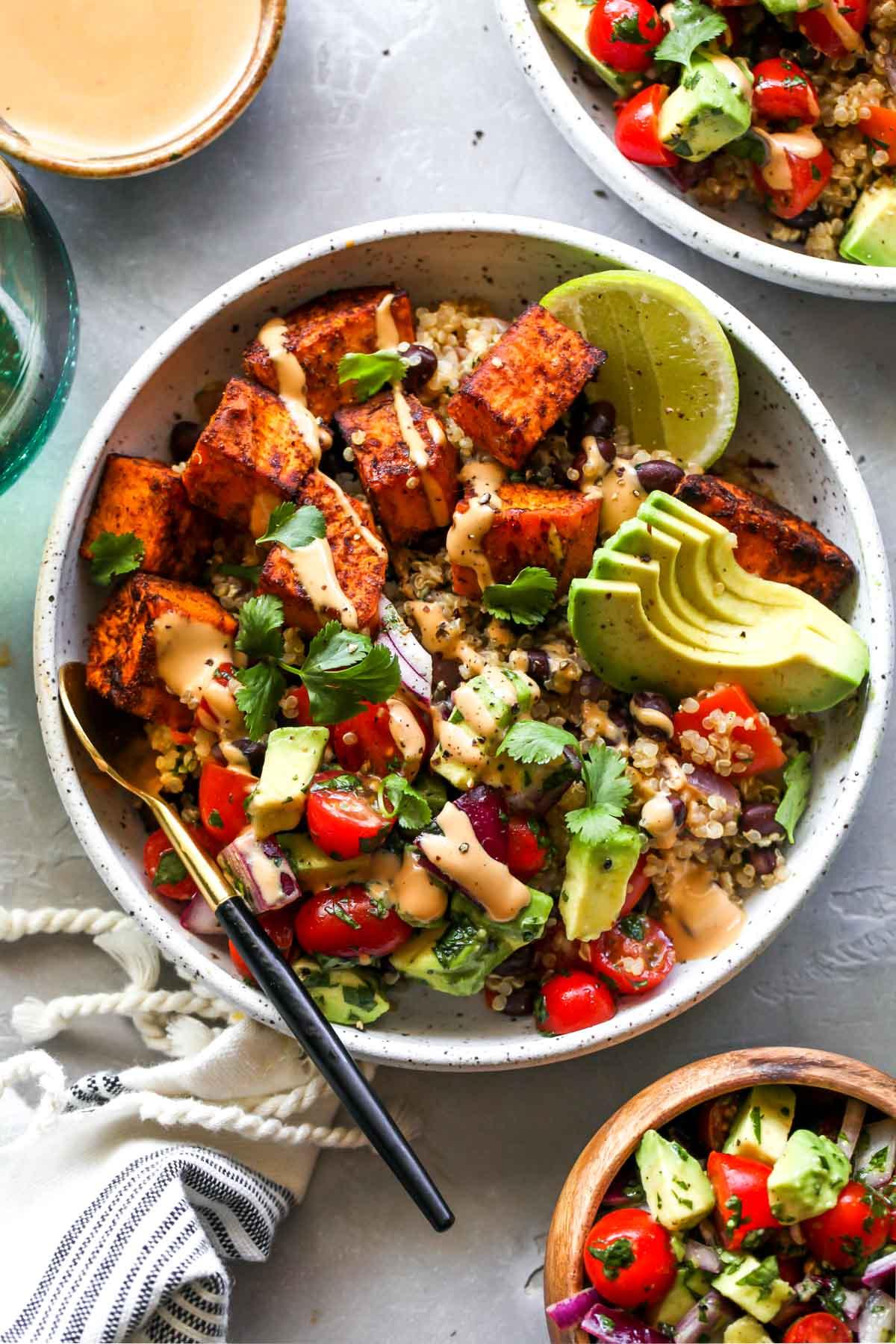 Sweet potato vegetarian burrito bowls topped with tahini sauce
