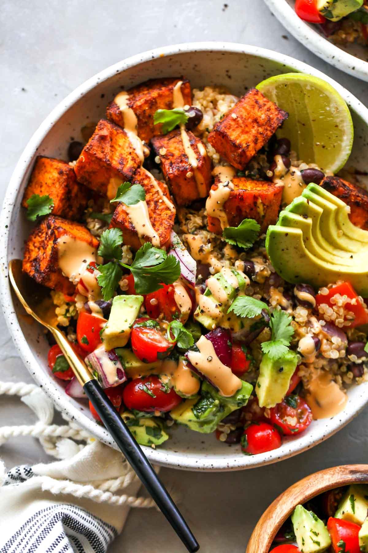 Sweet potatoes, quinoa, black beans, and pico de gallo in a white bowl