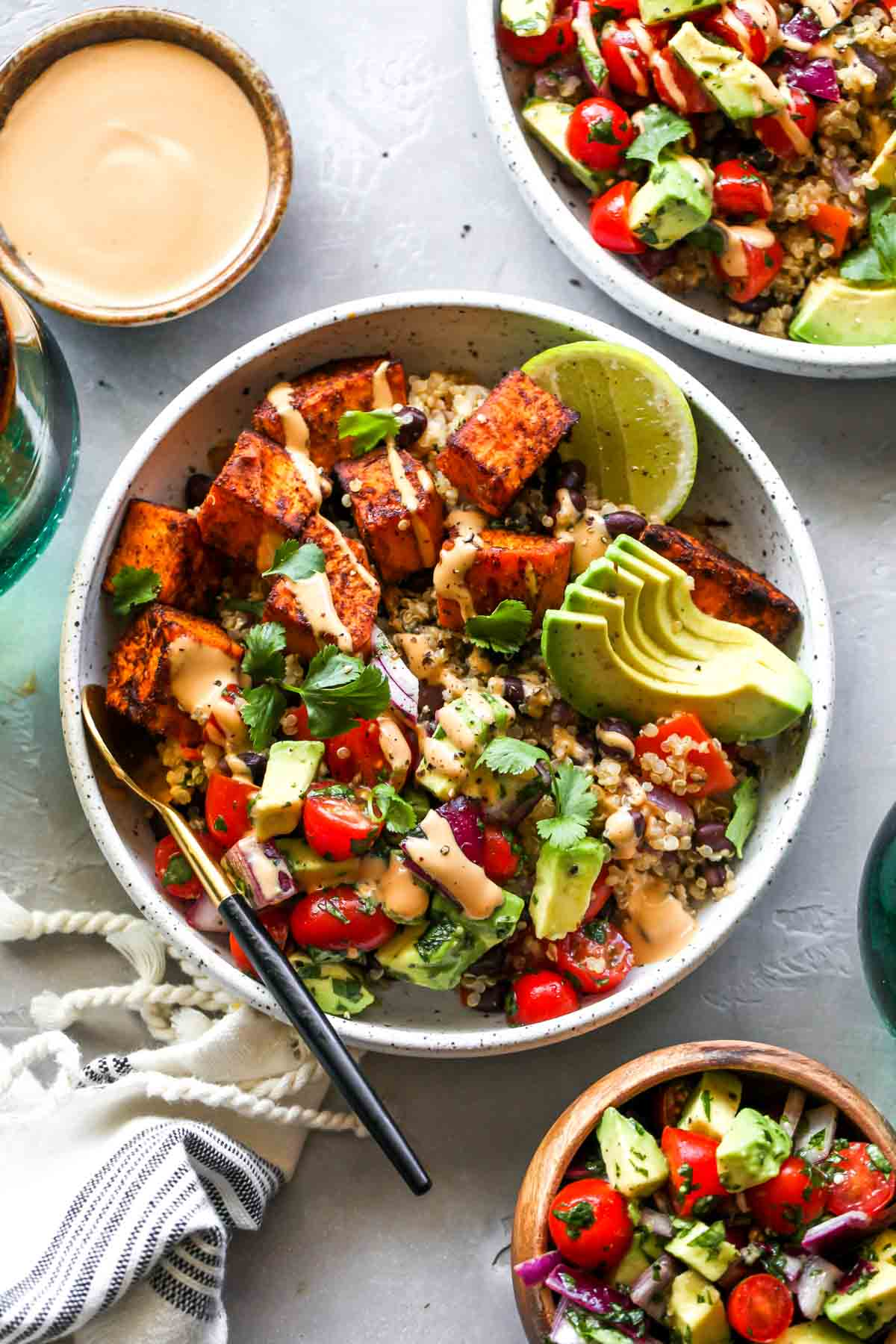 Assembled vegetarian burrito bowls with chipotle tahini sauce on the side