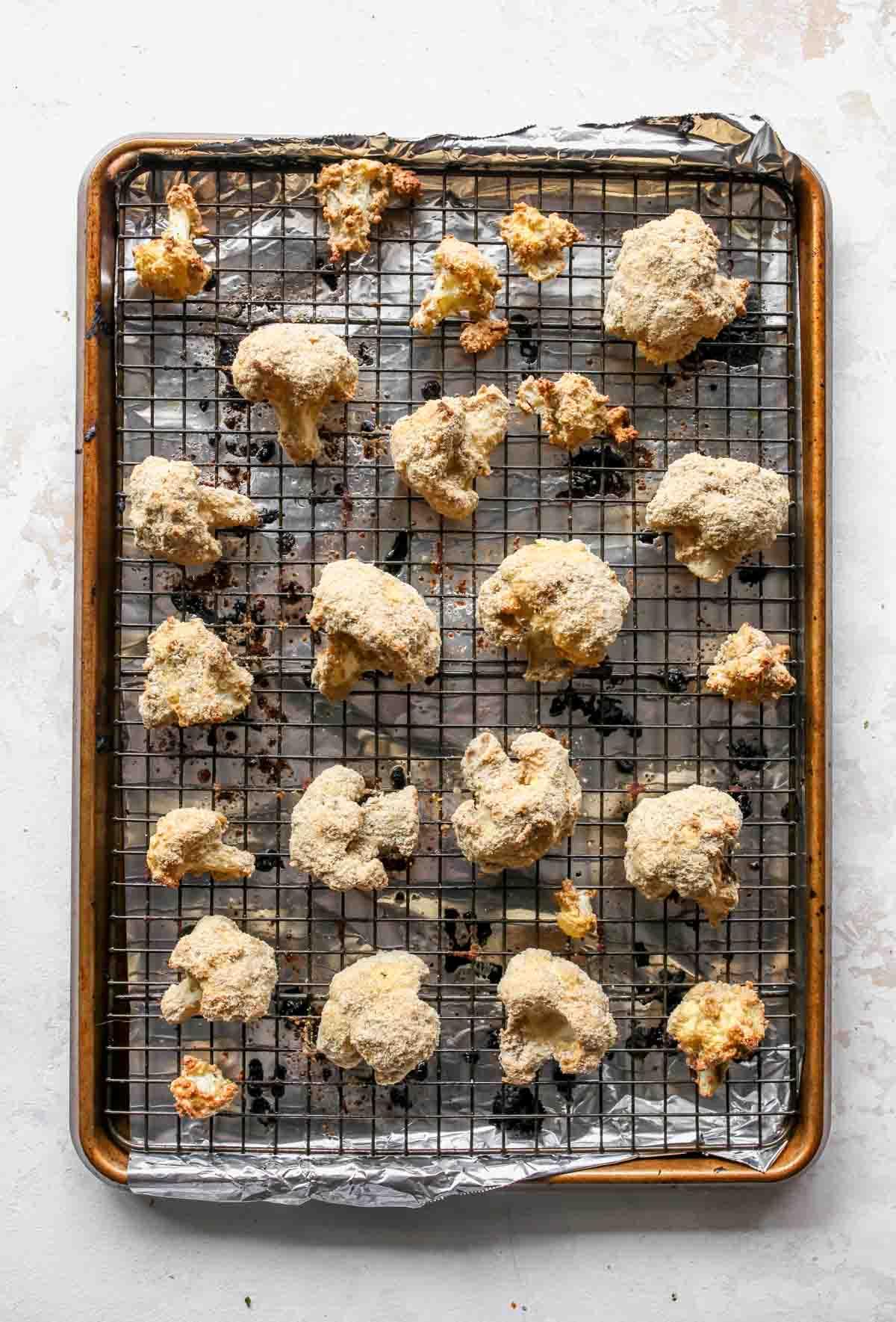Breaded cauliflower florets on a prepared baking sheet
