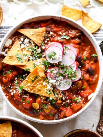 Mole Poblano Chili topped with radish, cilantro, and tortilla chips
