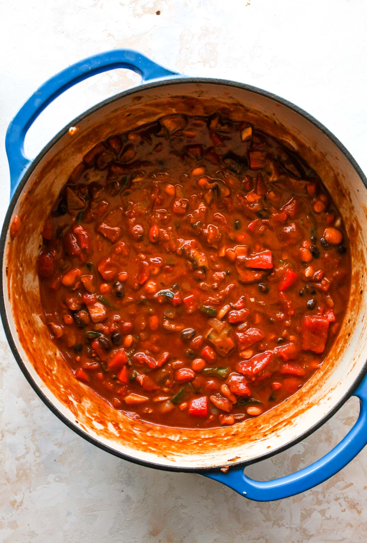 Tomato sauce, diced tomatoes, and beans being added to pot