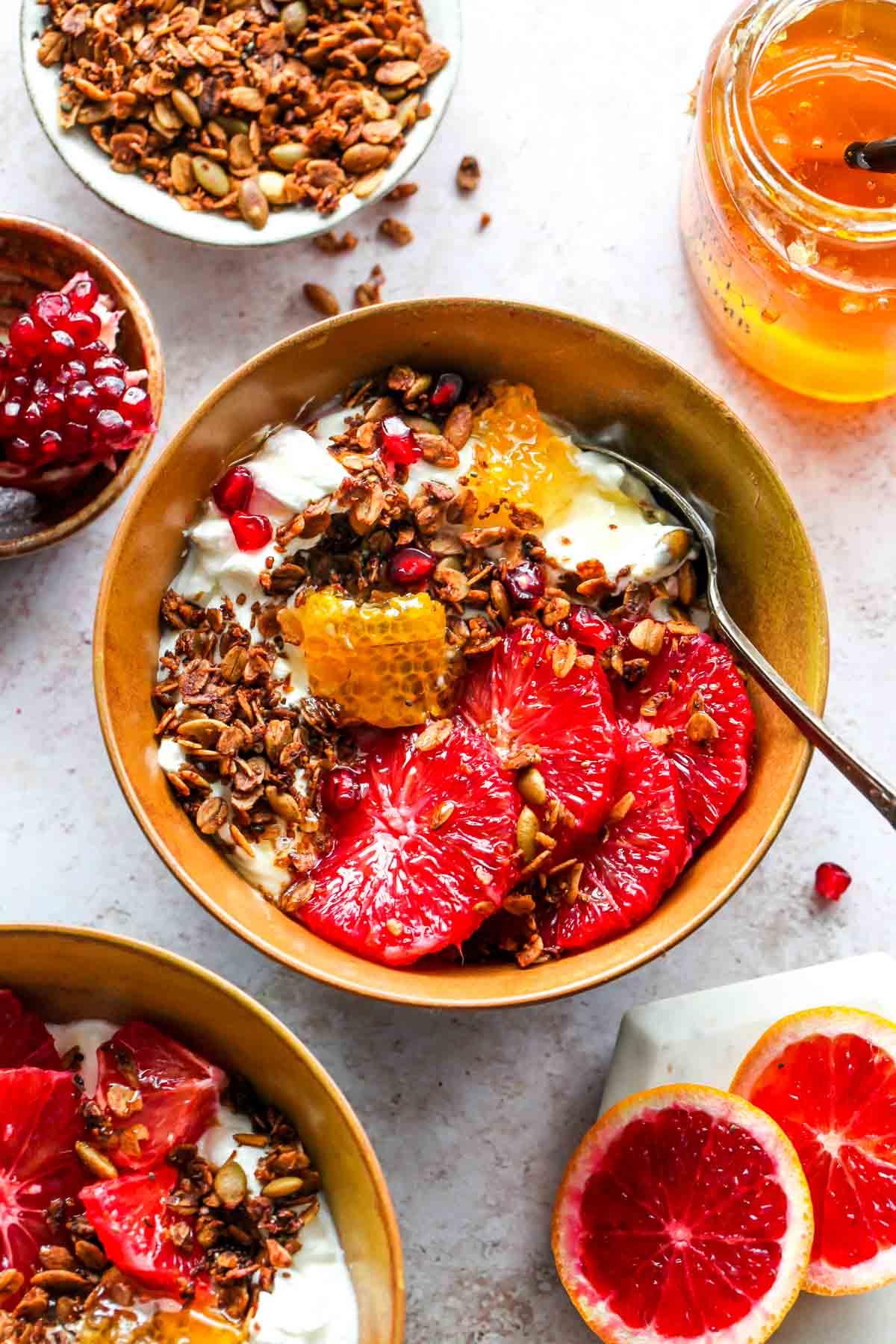 Yogurt bowl topped with citrus wedges, granola, and honey