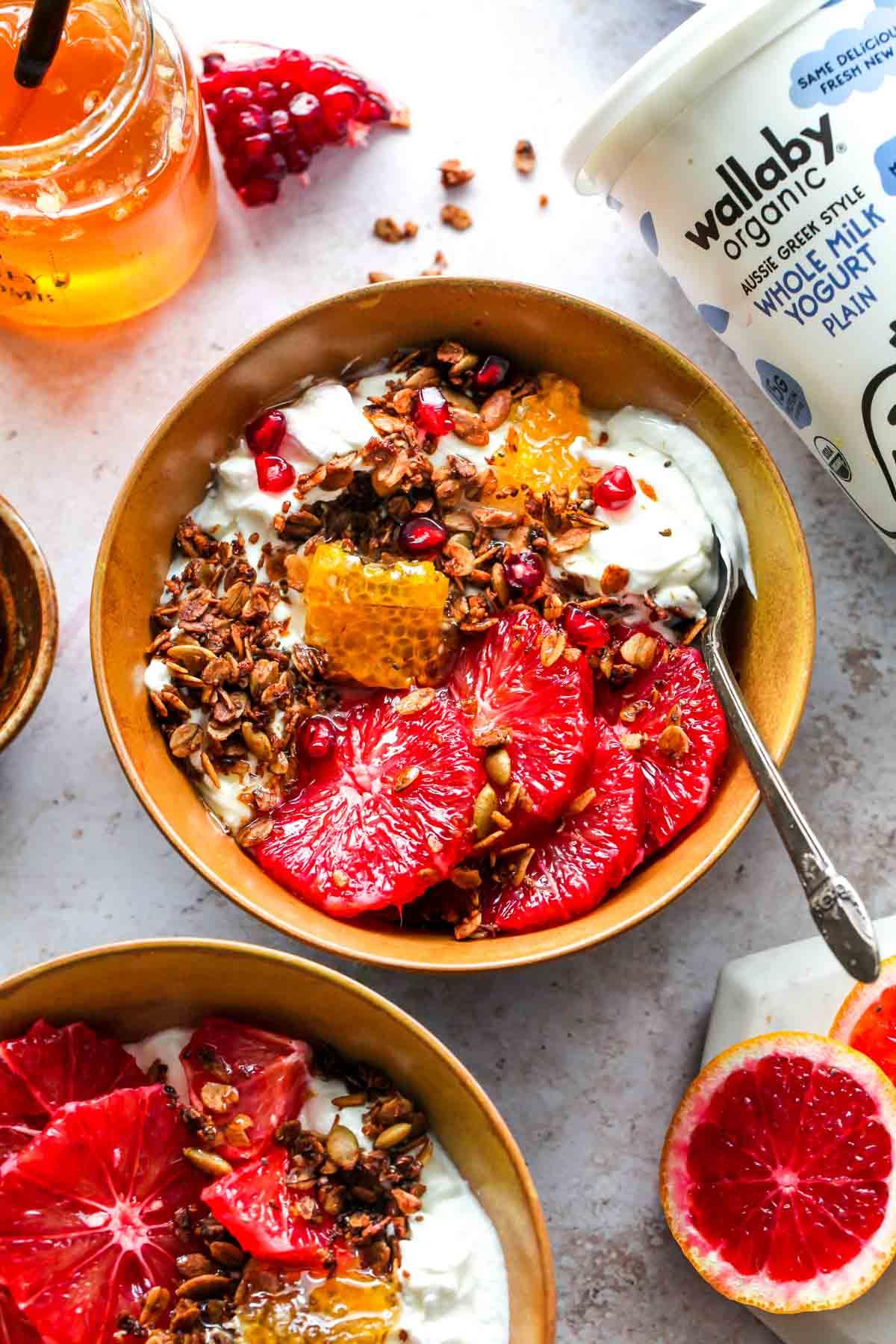 Breakfast spread including Wallaby yogurt, honey, citrus, and prepared breakfast bowls
