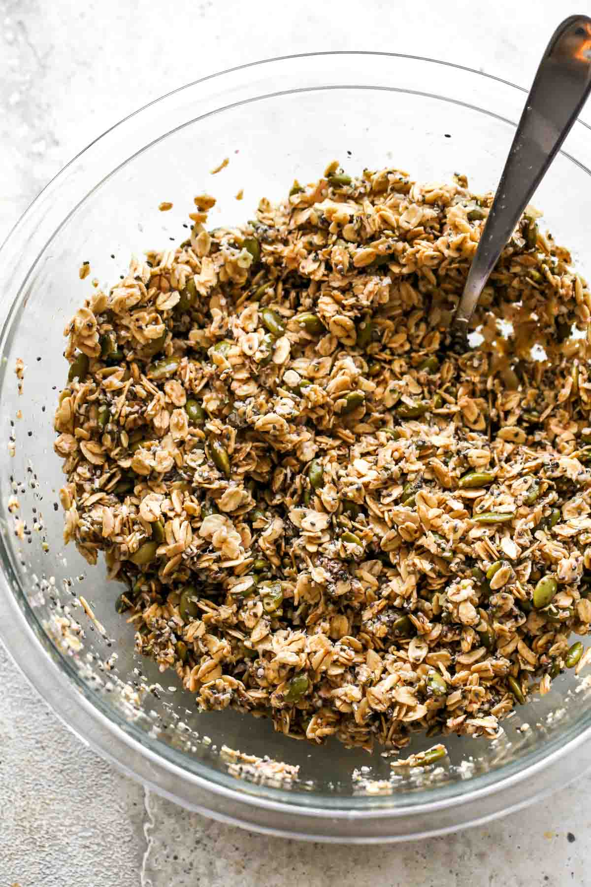 Oats, seeds, coconut, oil, and honey being mixed together with a spoon