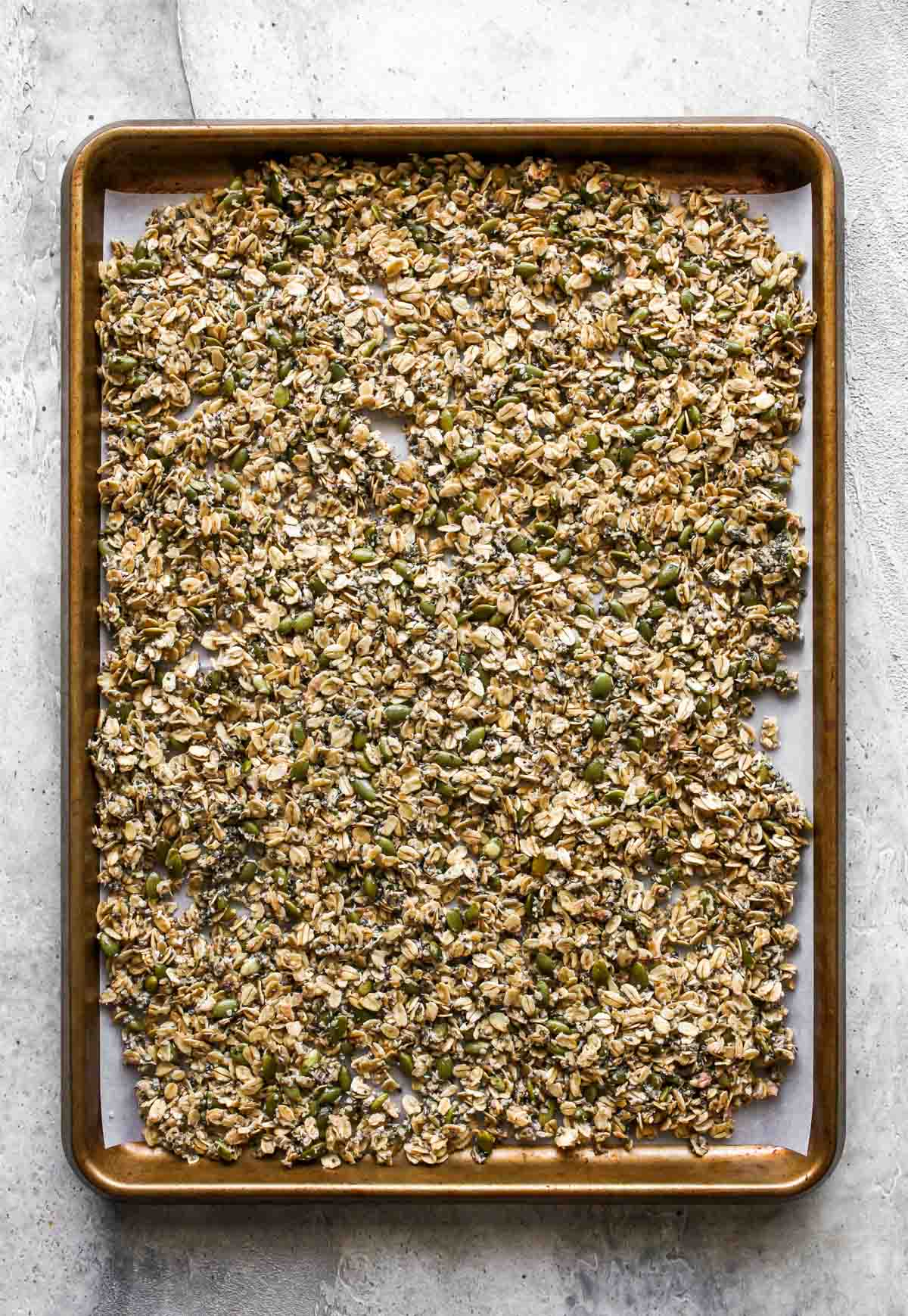 Raw granola being spread on a rimmed baking sheet and baked until golden