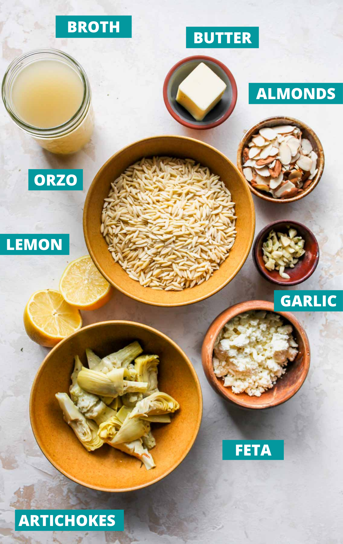 Orzo salad ingredients in separate bowls with blue labels