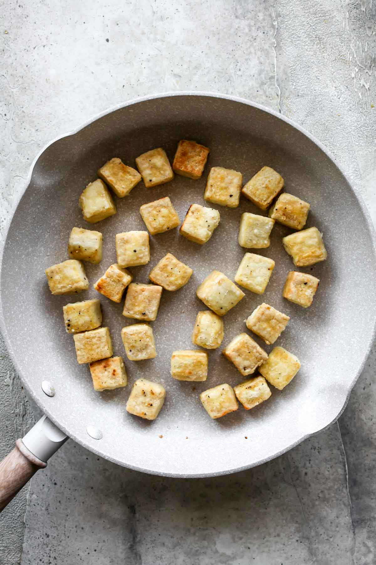 Tofu cubes sauteing in a white skillet