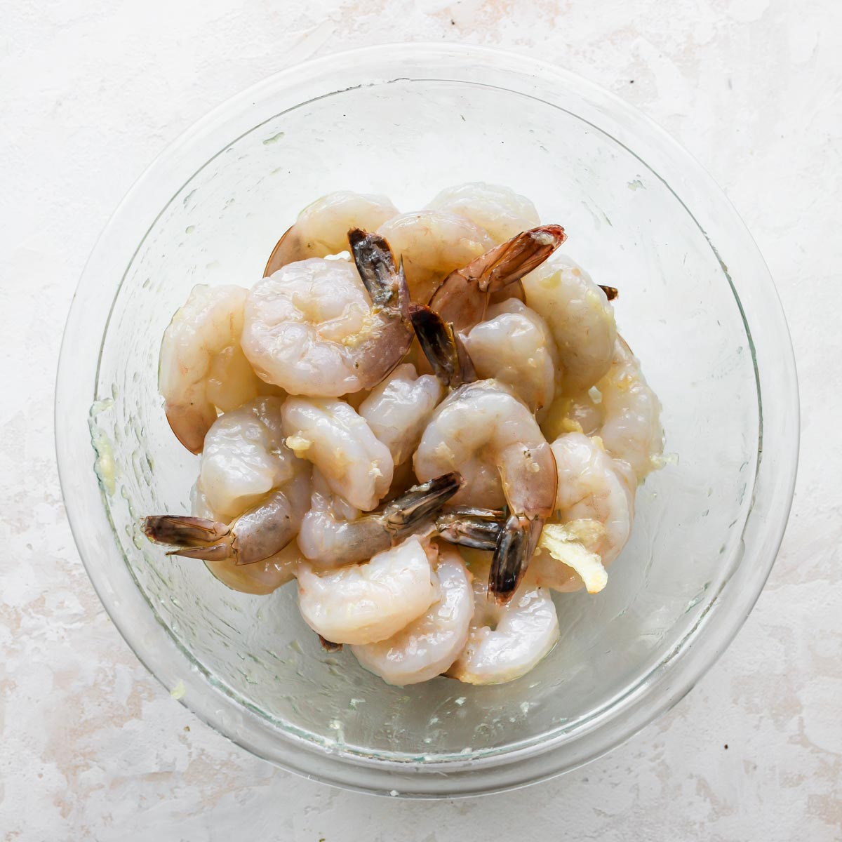 Shrimp being marinated in olive oil and garlic in a bowl
