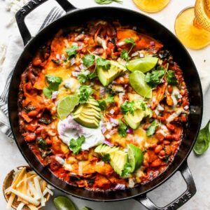 Spinach Artichoke Skillet Enchiladas topped with avocado, cilantro, and sour cream