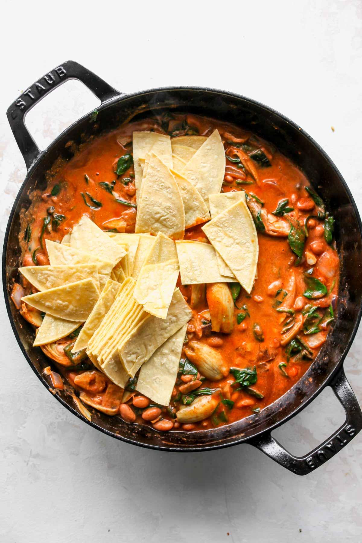 Strips of corn tortillas being mixed into a pan of enchiladas